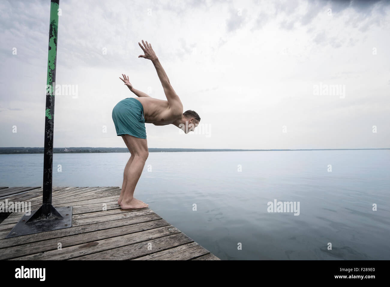 Mature man diving into water on pier, Baden-Wurttemberg, Bavaria, Germany - Stock Image