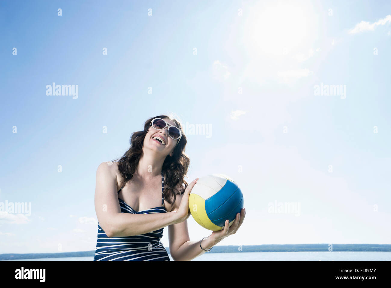 Mature woman playing volleyball on the beach, Bavaria, Germany Stock Photo