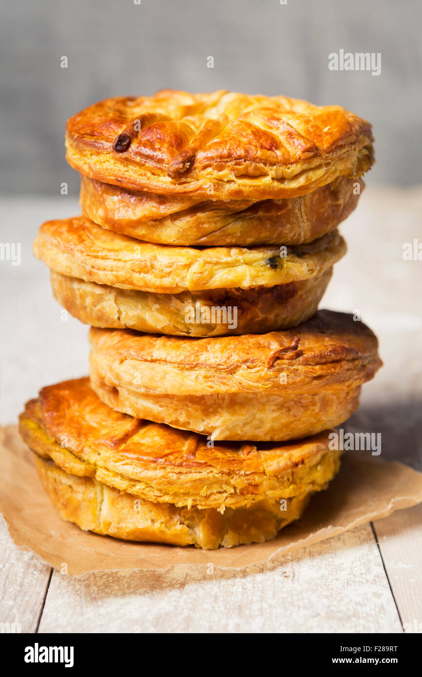 A stack of homemade meat pies on a rustic table. - Stock Image