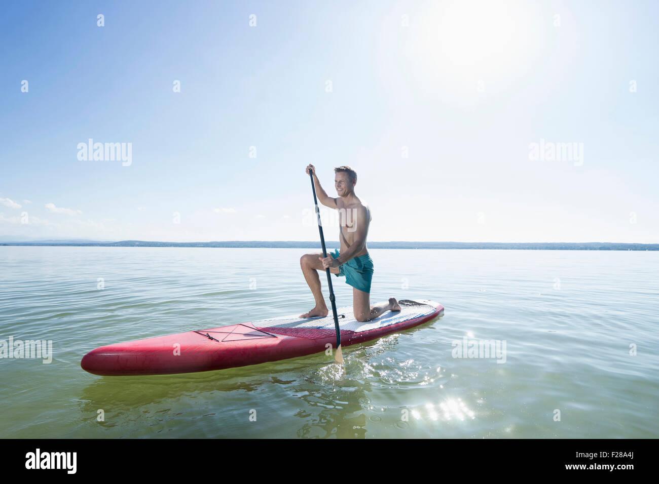 Mature man paddleboarding in the lake, Bavaria, Germany - Stock Image