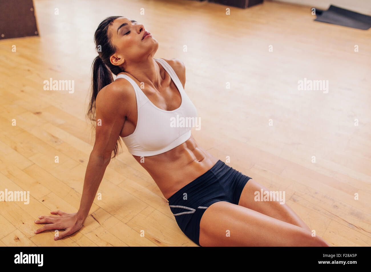 Portrait of tired woman having rest after workout. Tired and exhausted female athlete sitting on floor at gym. - Stock Image