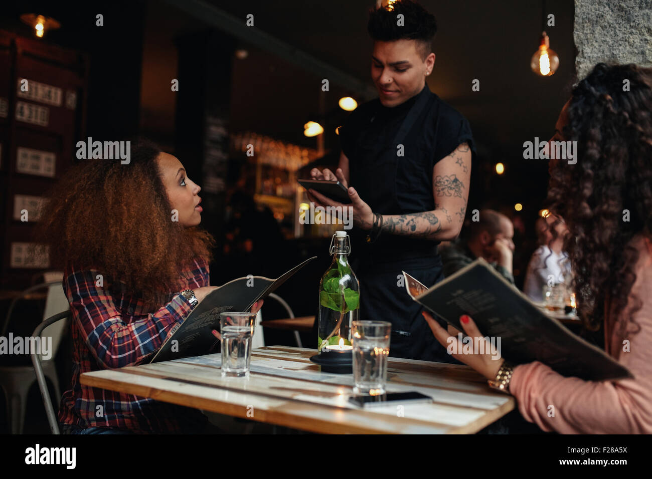 Portrait of a young woman giving an order to a waiter at a cafe sitting with her friend. Waiter putting order onto - Stock Image