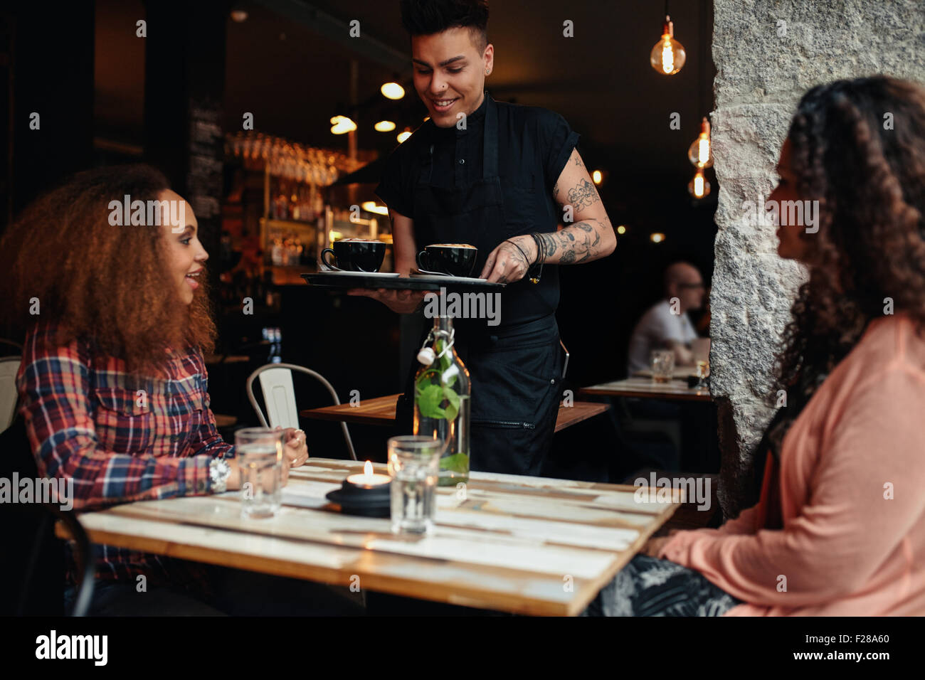 Tow young women sitting at a restaurant, with waiter serving coffee. Female friends at coffee shop. - Stock Image