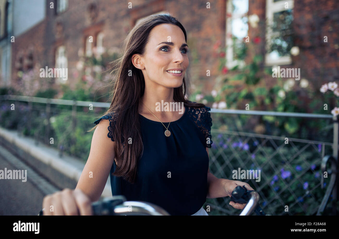 Outdoor shot of happy young woman walking down the street with a cycle looking away. - Stock Image