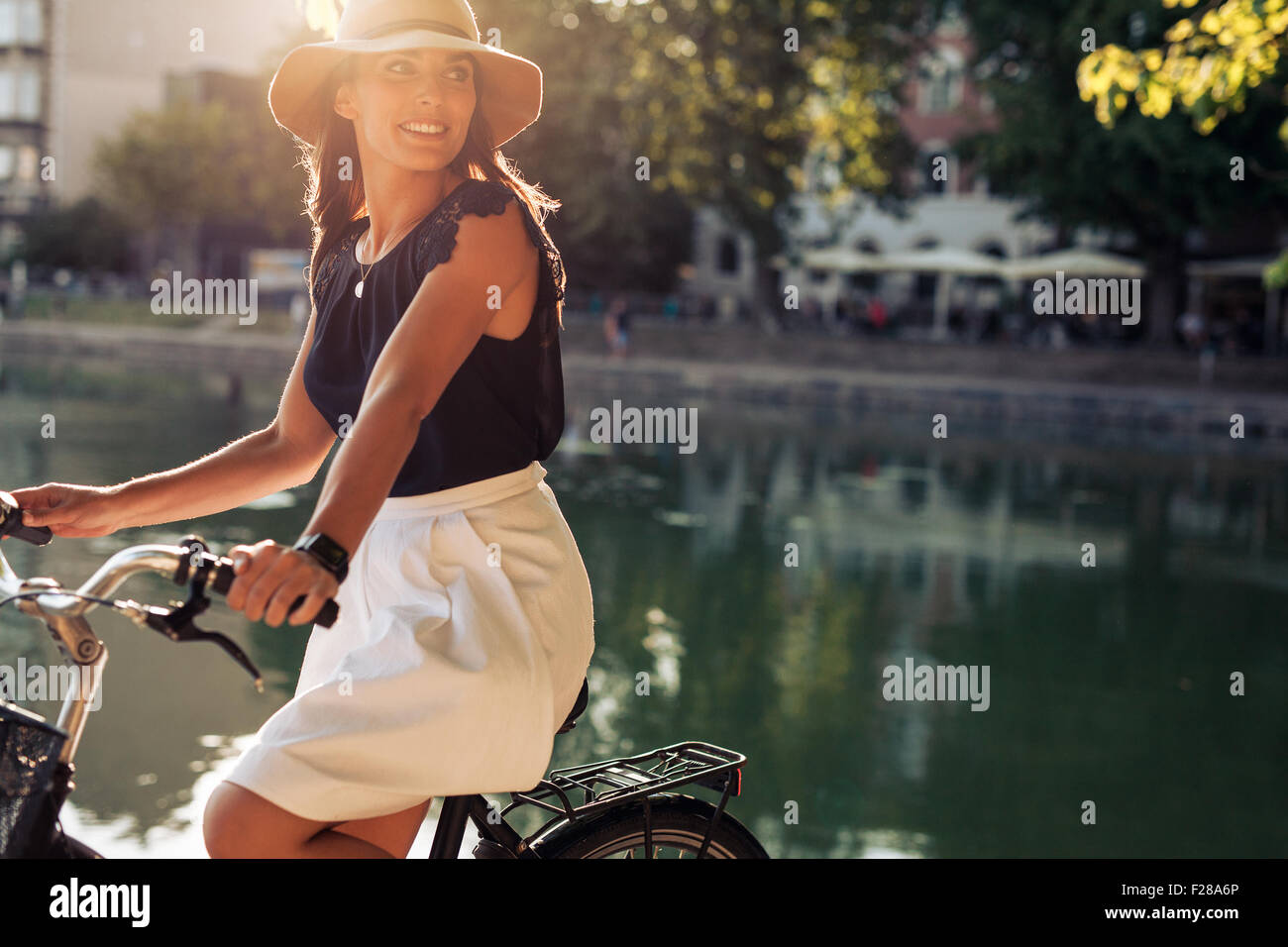 Portrait of happy young female cycling by a pond looking away smiling. Woman wearing a hat on a summer day riding - Stock Image