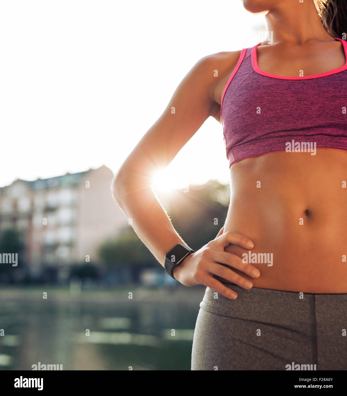 Close up shot of fitness model torso, she is wearing smartwatch standing with her hands on hips. Female athlete - Stock Image