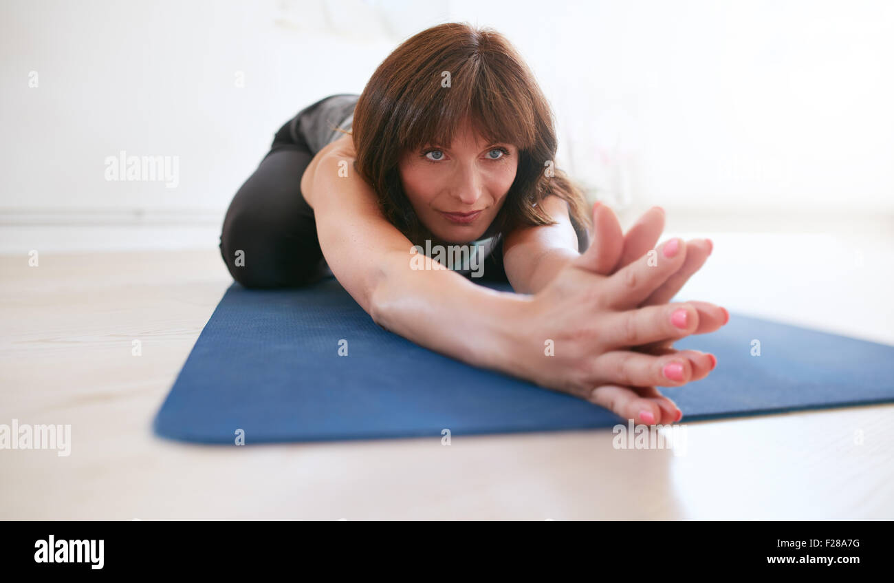 Woman stretching forward with her hands joined looking away. Female fitness trainer performing balasana yoga at - Stock Image