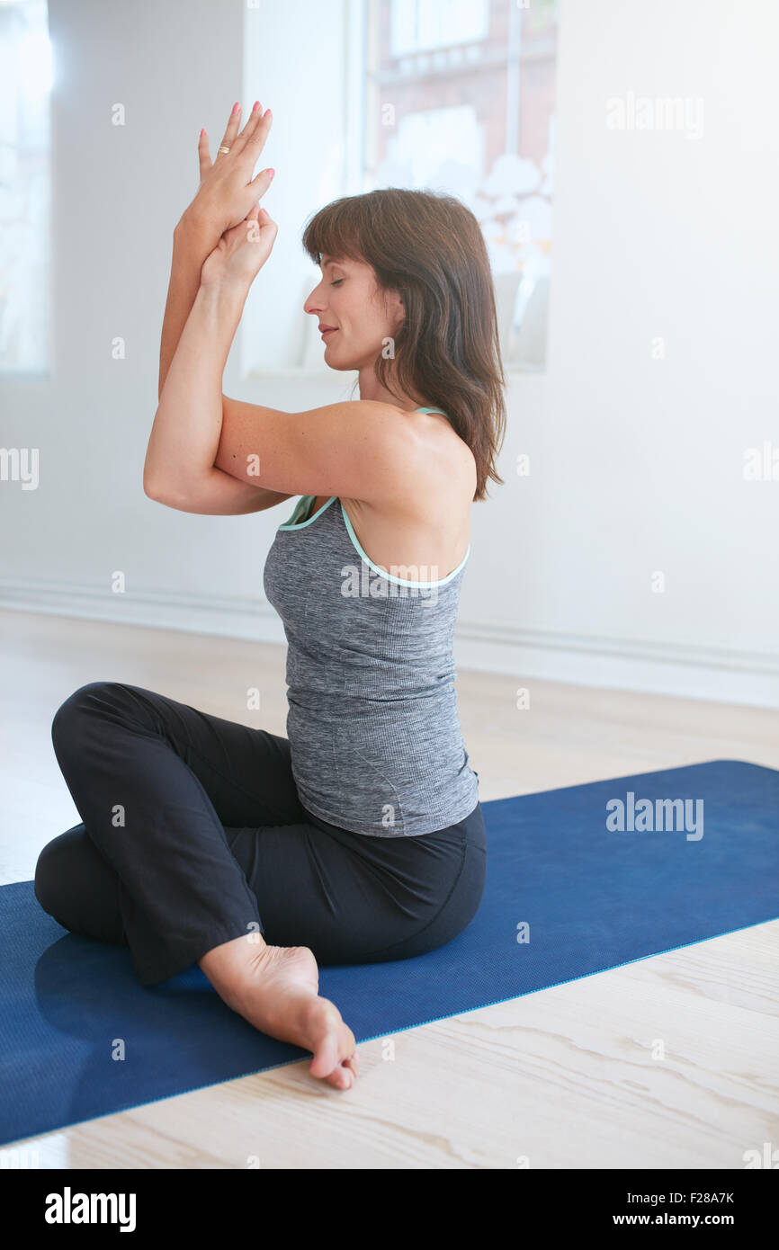 Woman practicing yoga, Garudasana, Eagle pose. Mature woman sitting on mat doing yoga with her arms and legs crossed. - Stock Image