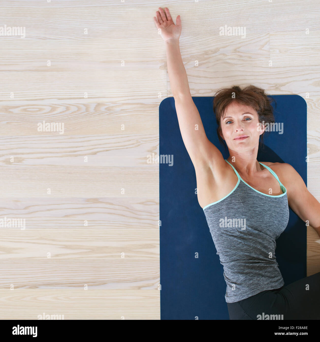 Top view of woman lying and stretching on exercise mat. Female on floor twisting her body and stretching her one - Stock Image