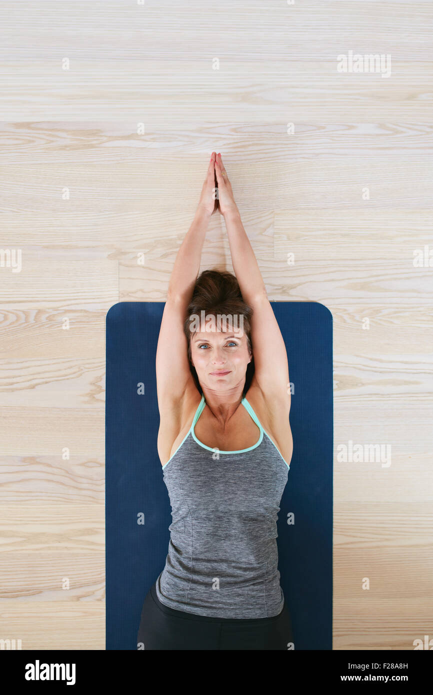 Top view of woman lying on floor doing stretching exercise. Fitness woman exercising on yoga mat. - Stock Image