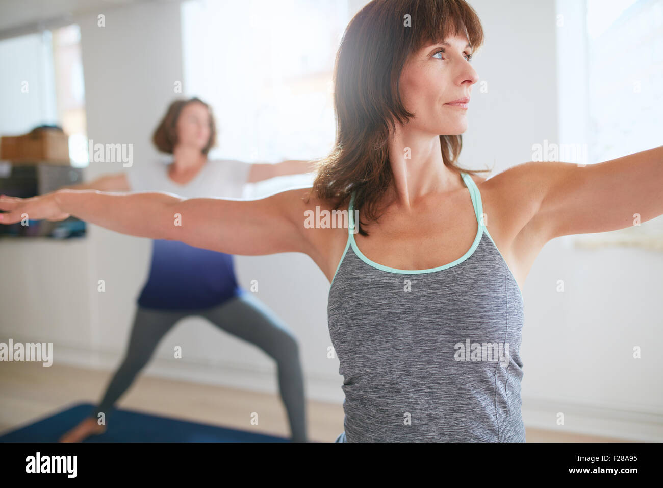 Fitness trainer doing the warrior pose during yoga class. Yoga teacher performing Virabhadrasana position in gym Stock Photo