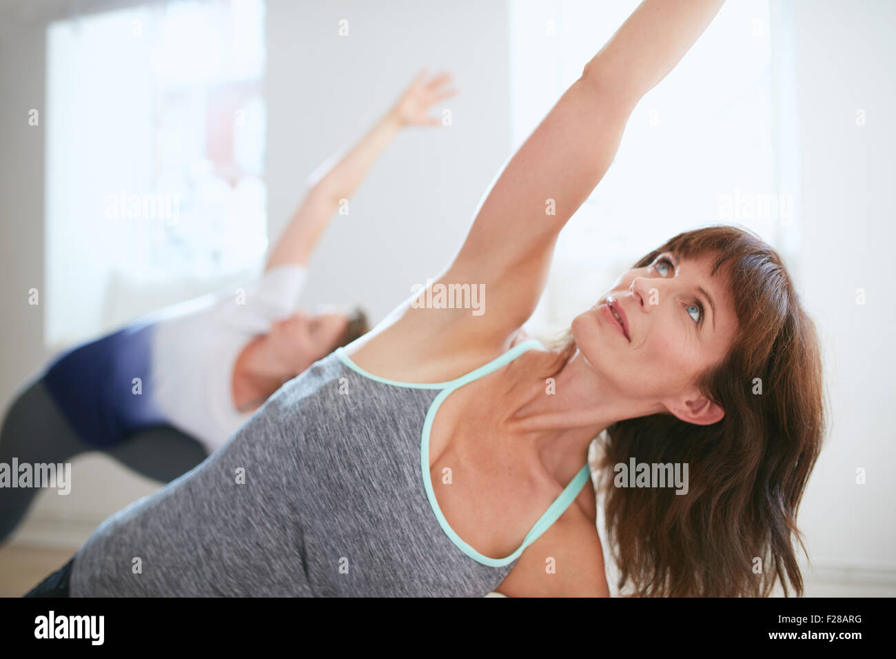 Portrait of mature woman practicing yoga at gym. Fitness female doing Triangle yoga Pose, Trikonasana. Stock Photo