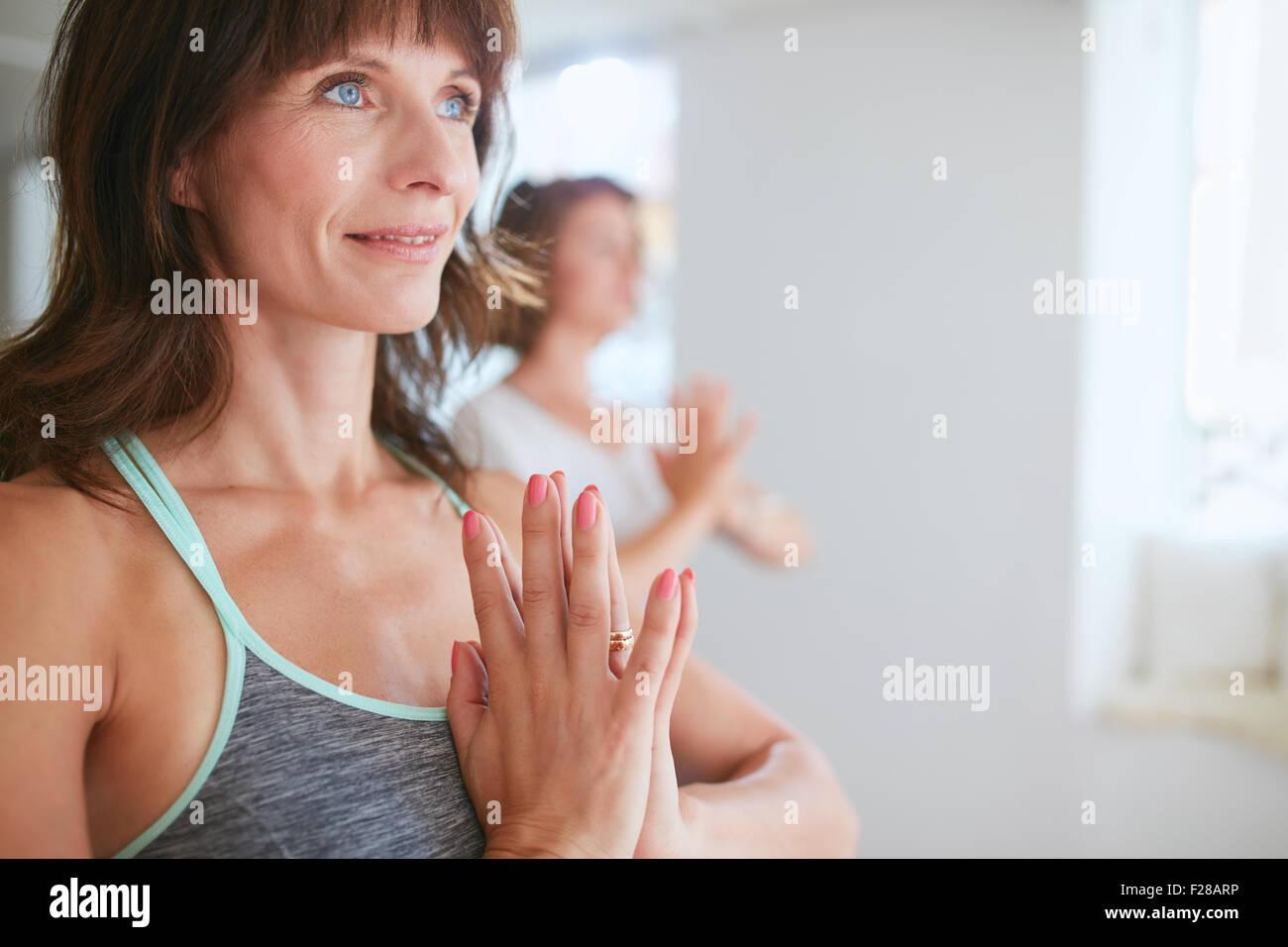 Close up shot of happy mature woman doing yoga looking away smiling. Women in yoga pose vrikshasana using Namaste. - Stock Image