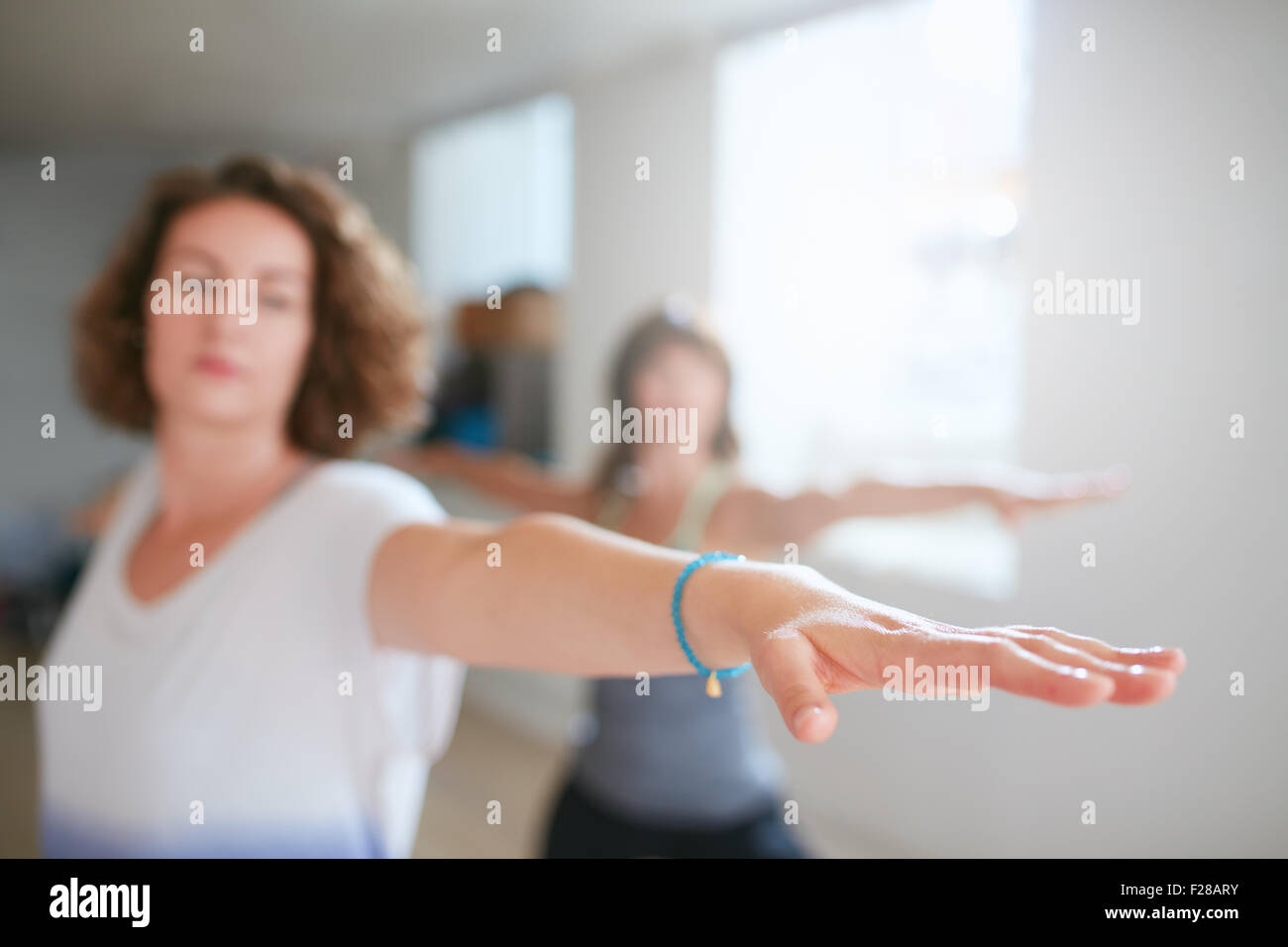 Fitness woman stretching her arms at yoga class. Young woman performing yoga in warrior pose. Virabhadrasana. Focus - Stock Image