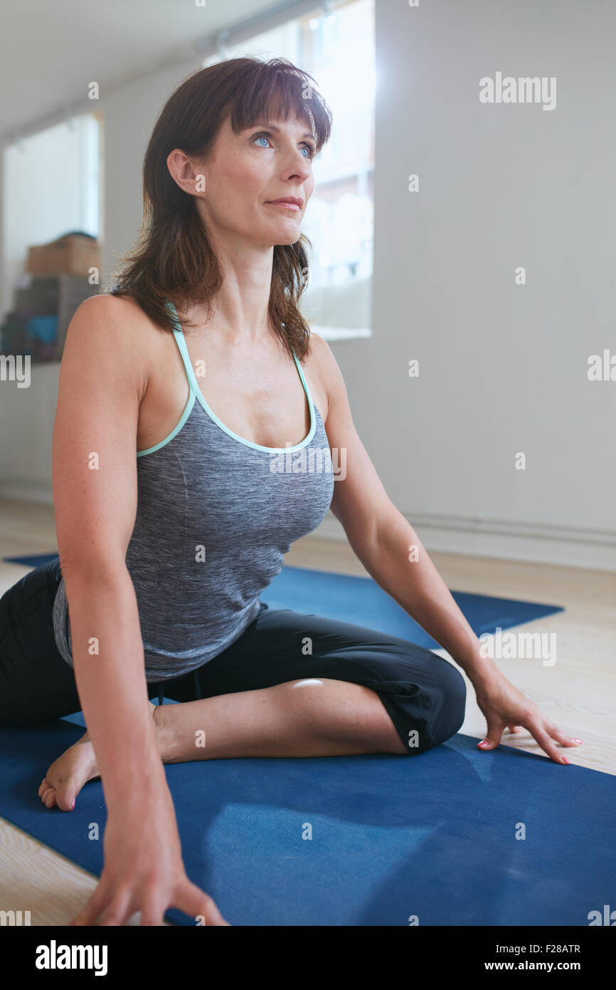 Portrait of fit woman doing chest opener yoga pose at gym with her one leg bend and another stretched on exercise - Stock Image