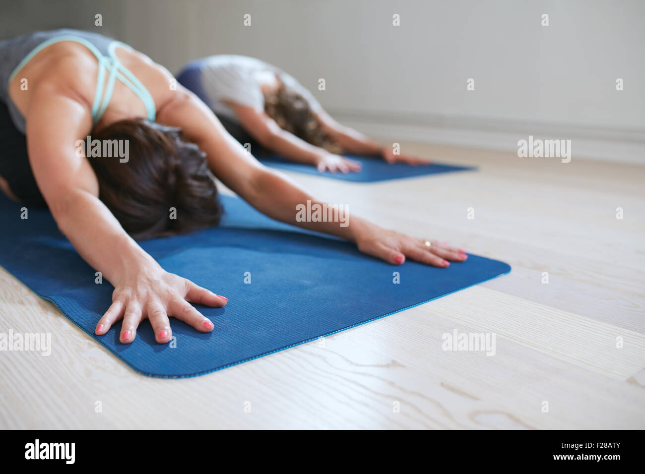 Two women doing stretching workout on fitness mat. Females performing yoga on exercise mat at gym. Child Pose, Balasana. - Stock Image
