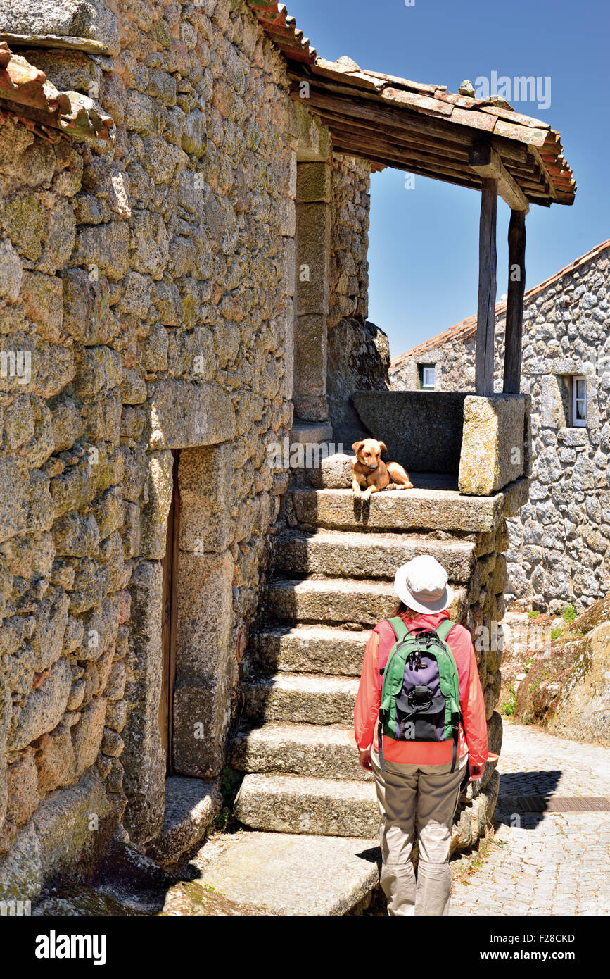 Portugal: Woman looking to dog at the staircase of a stone house in the historic village Monsanto - Stock Image
