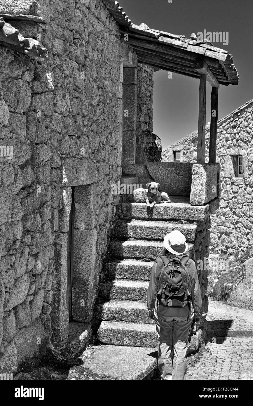 Portugal: Woman looking to dog at the staircase of a stone house in the historic village Monsanto (bw) Stock Photo