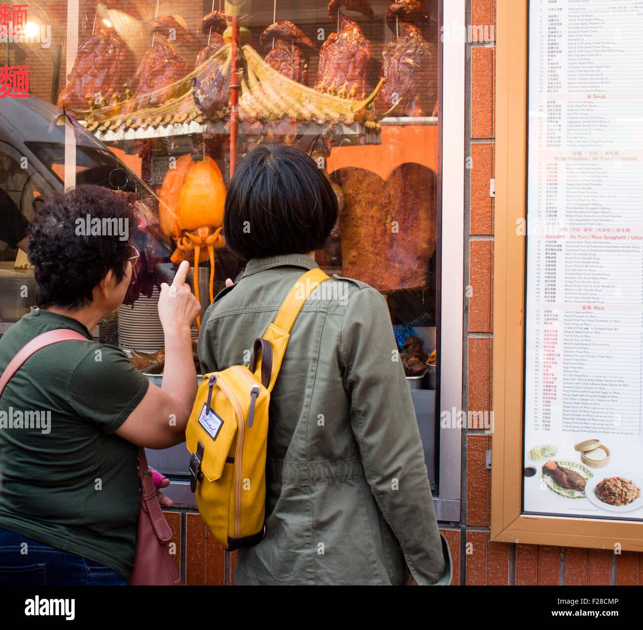 Chinese woman looking at crispy duck in restaurant window. Gerrard Street, London UK - Stock Image