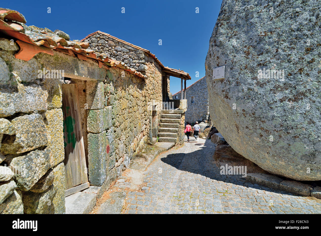 Portugal Tourists Walking In A Alley With Rustic Stone Houses And Huge Granite Rocks Monsanto