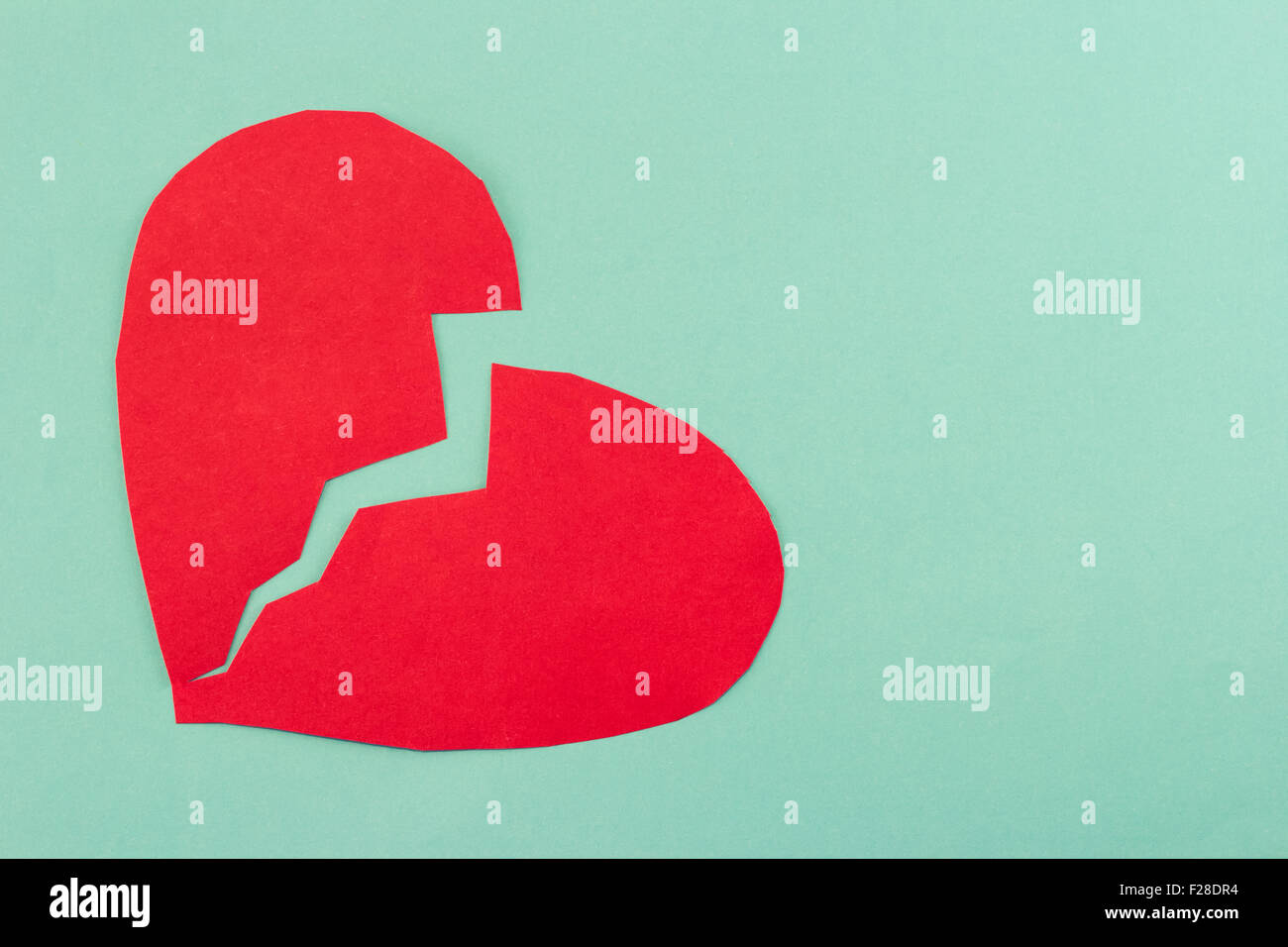 close up of paper broken heart on blue background - Stock Image