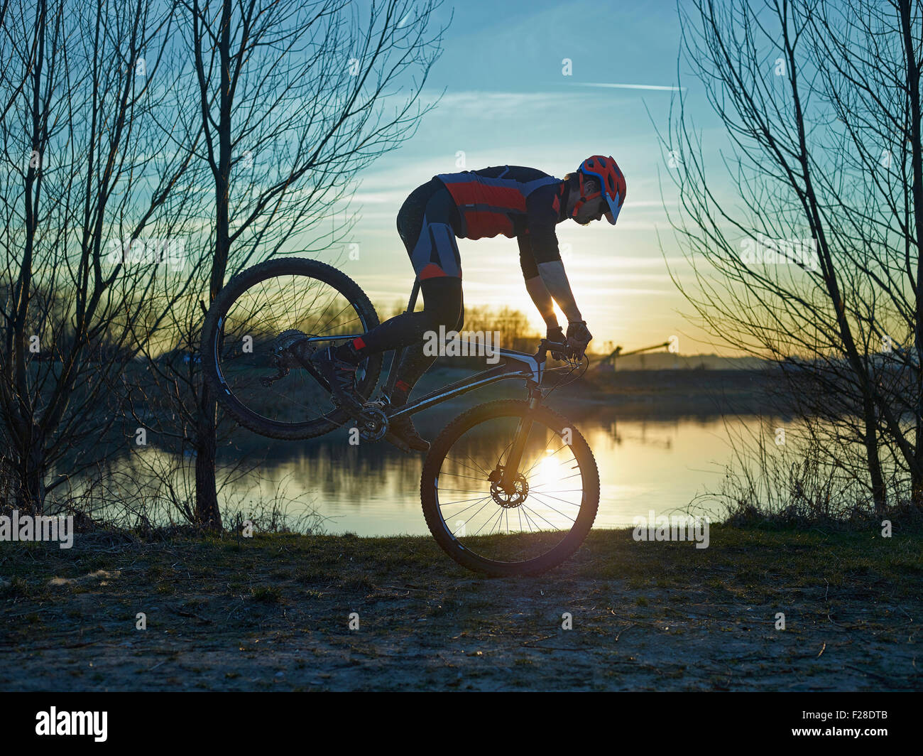 Mature man doing stunts on mountain bike during sunset, Bavaria, Germany - Stock Image