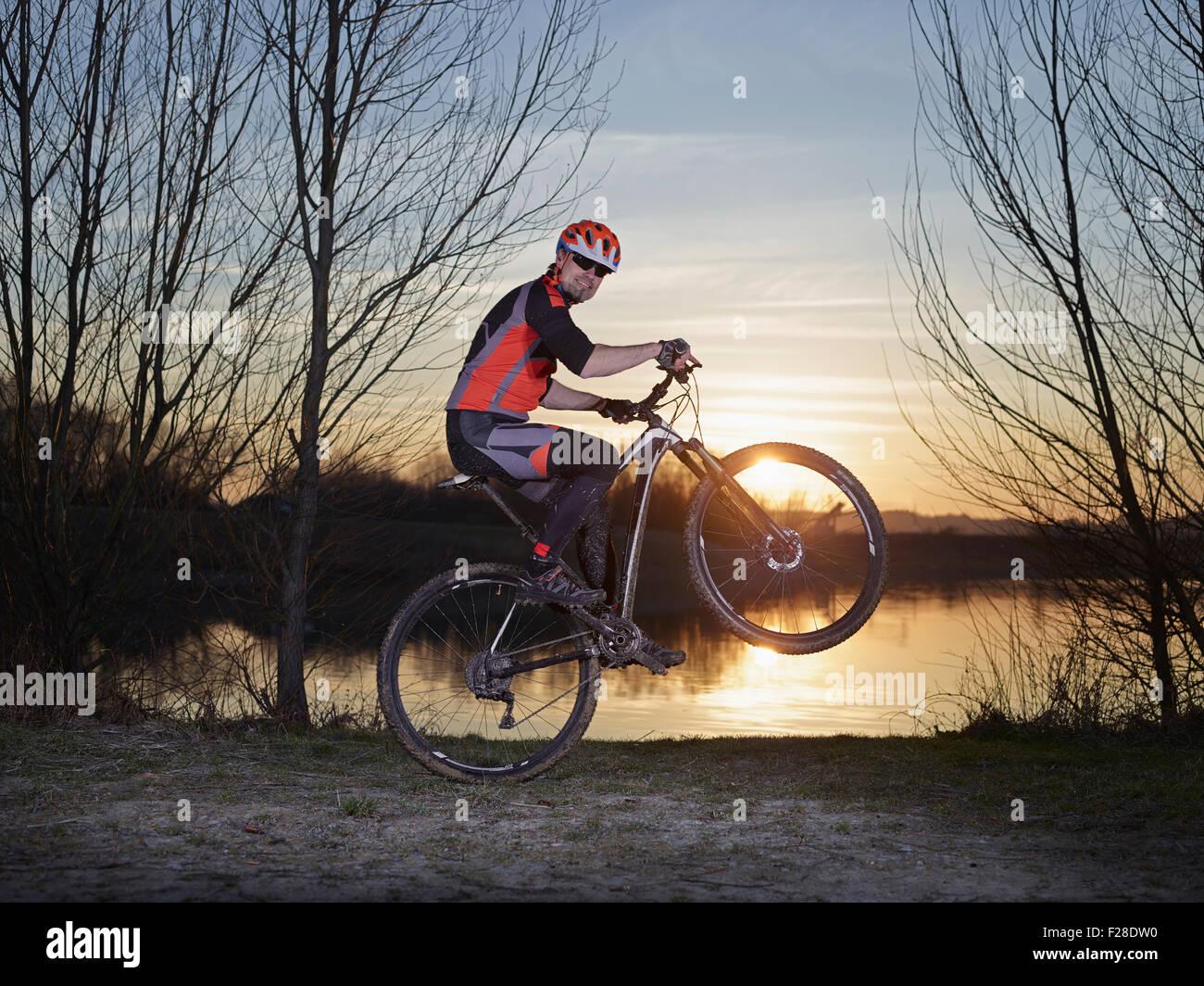 Mature man doing stunts on mountain bike during sunset, Bavaria, Germany Stock Photo
