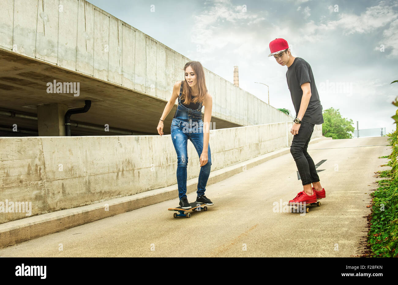 Skateboarder woman and man rolling down the slope - Stock Image