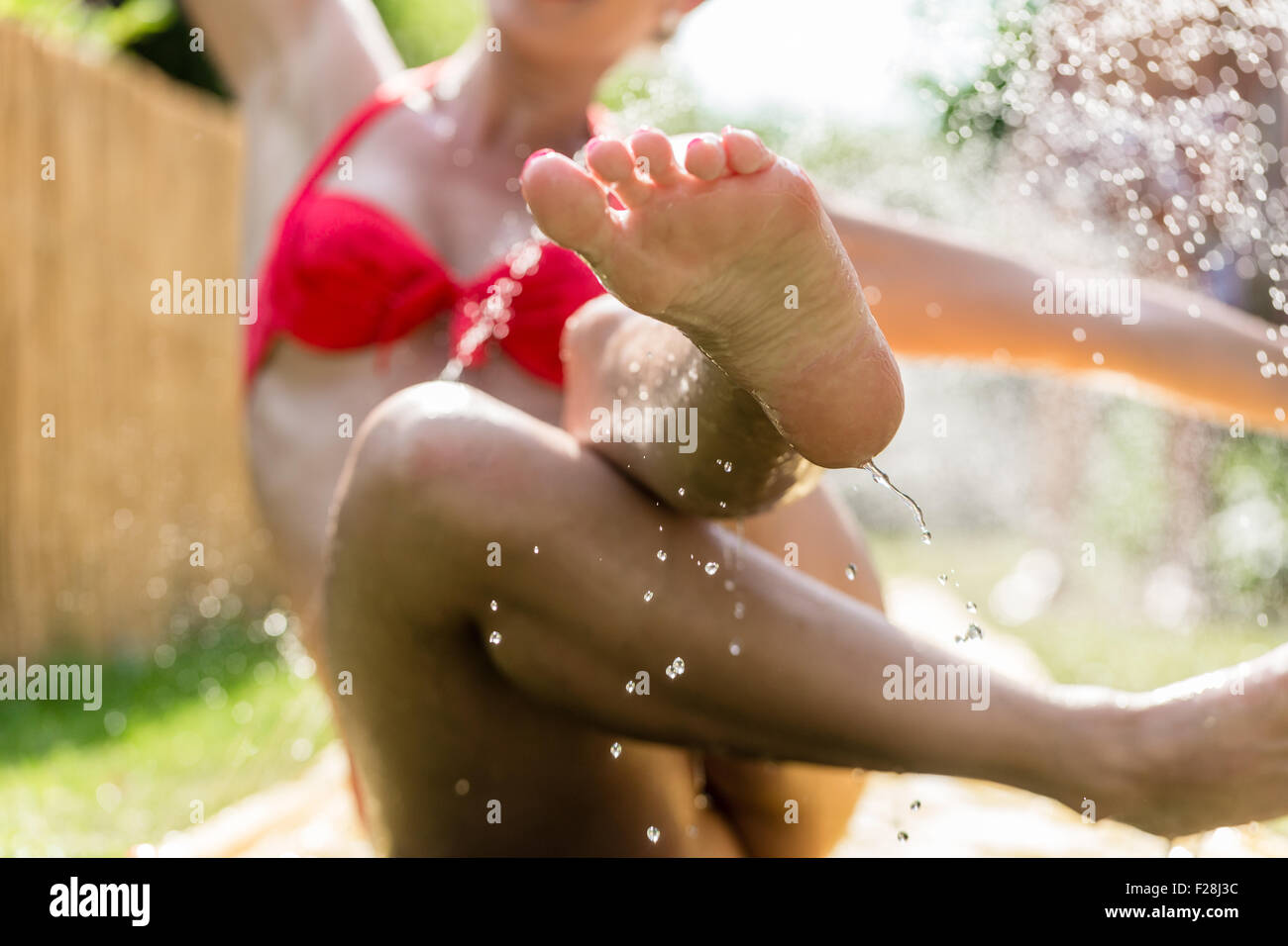 woman cooling down in garden with sprinkler splashing water drops around - Stock Image