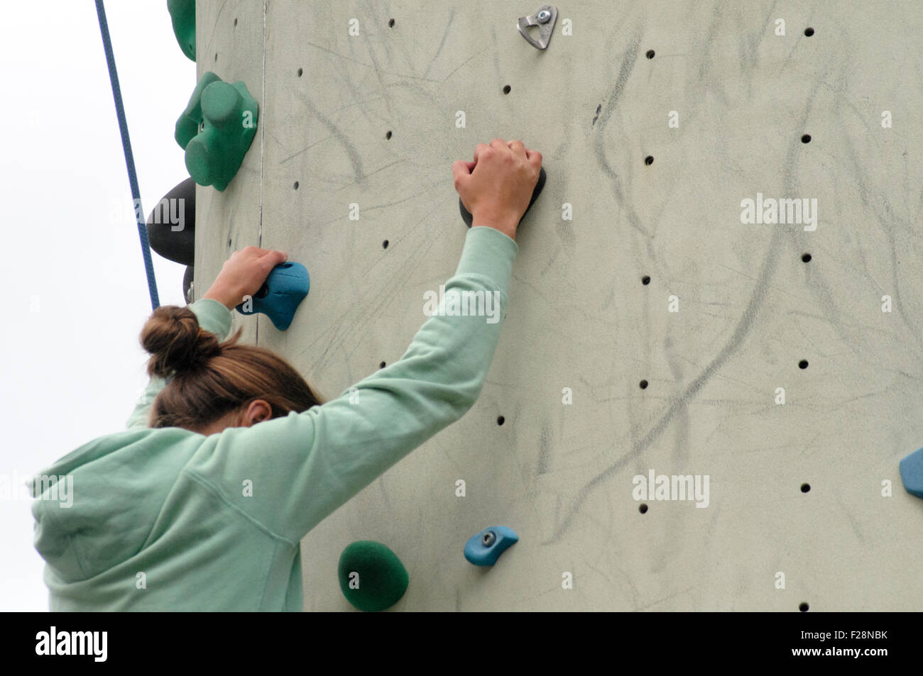 Young teen girl climbs up an artificial climbing wall close up of the hands - Stock Image