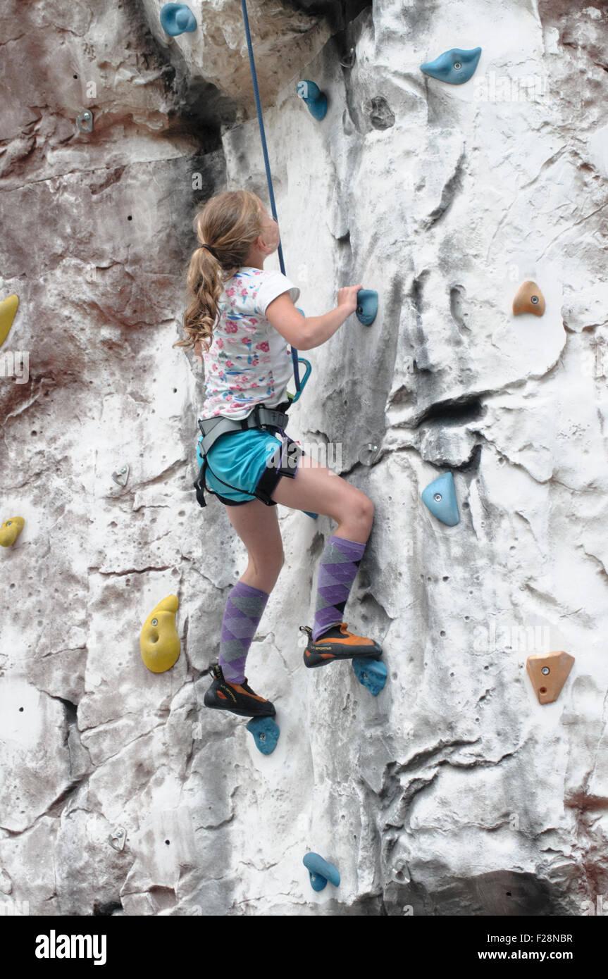 Young teen girl climbs up an artificial climbing wall - Stock Image