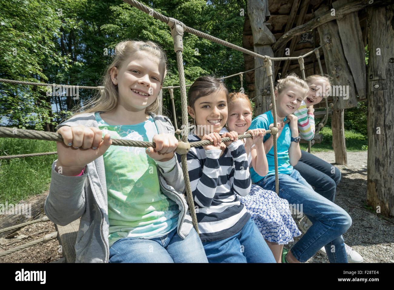 Girls sitting on rope bridge in playground, Munich, Bavaria, Germany - Stock Image