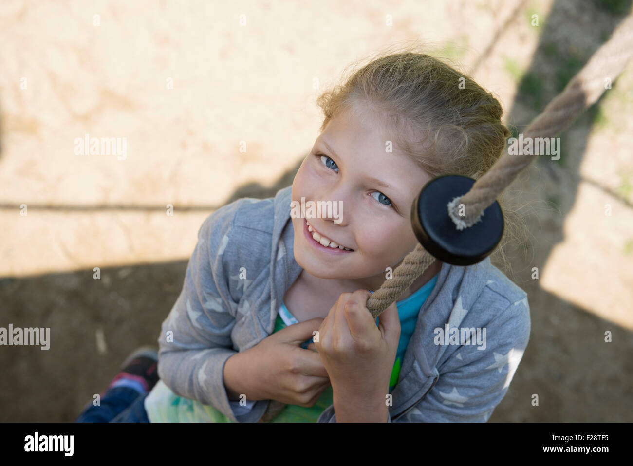 Girl climbing on rope in playground, Munich, Bavaria, Germany - Stock Image