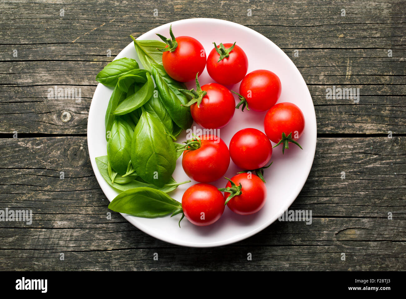 tomatoes and basil leaves on plate - Stock Image