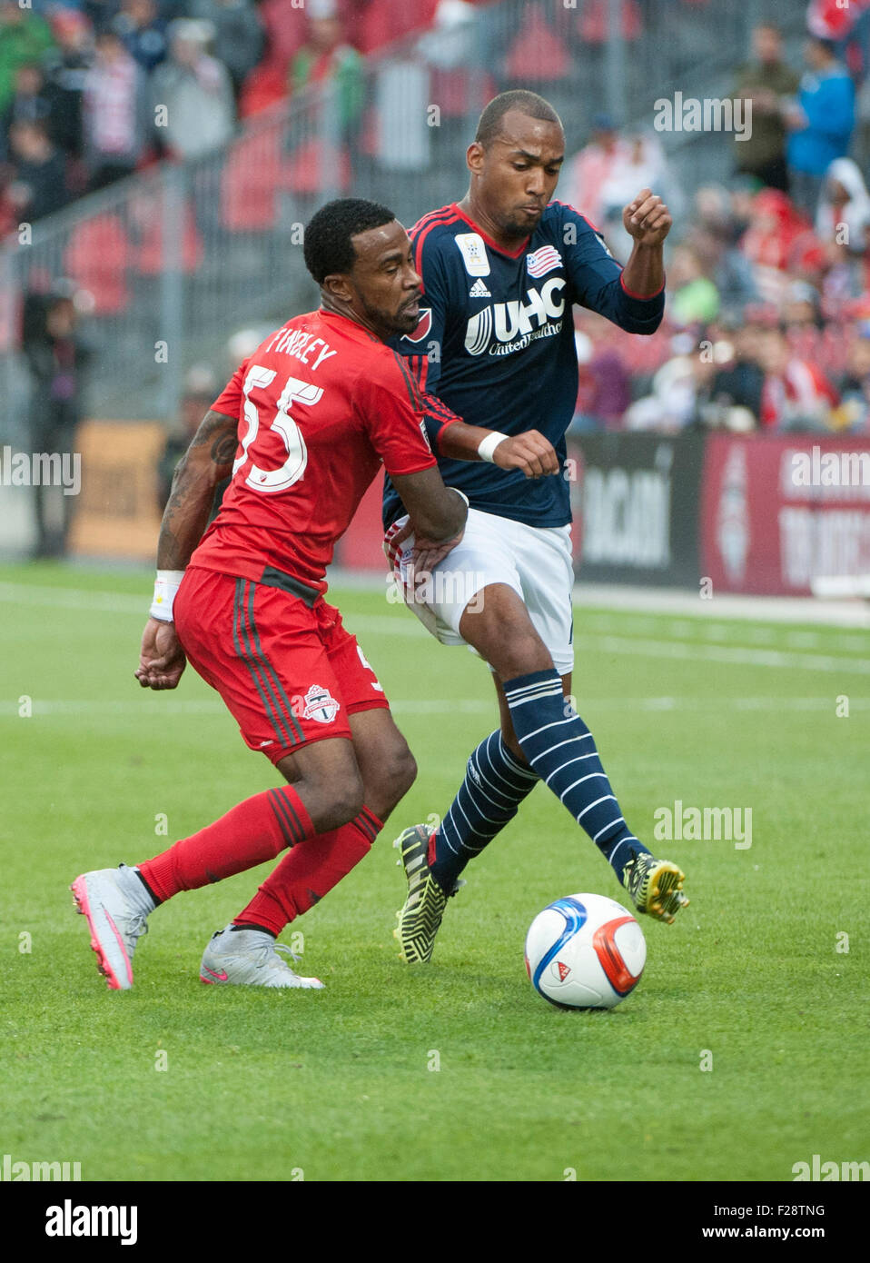 Toronto, Ontario, Canada. 13th September, 2015. Toronto FC forward Robbie Findley (55) tackles New England Revolution - Stock Image