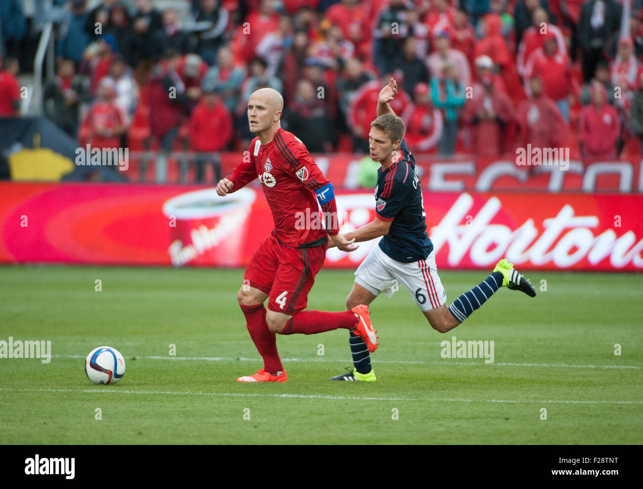 Toronto, Ontario, Canada. 13th September, 2015. Toronto FC midfielder Michael Bradley (4) chased by New England - Stock Image