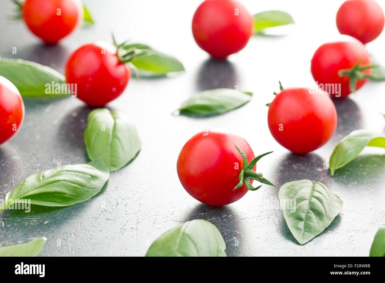 tomatoes and basil leaves on kitchen table - Stock Image
