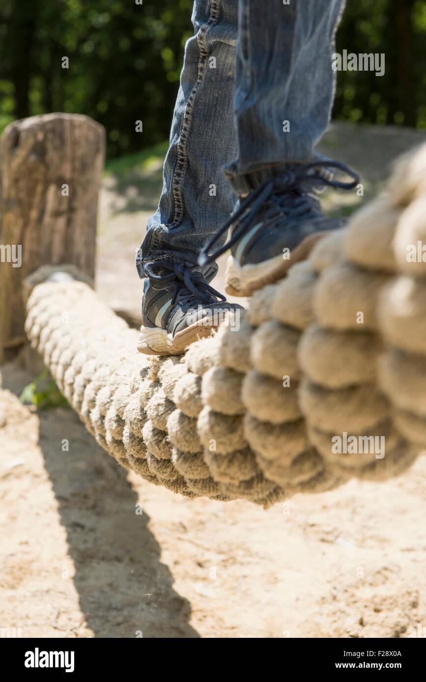 Girl balancing on rope in playground, Munich, Bavaria, Germany - Stock Image