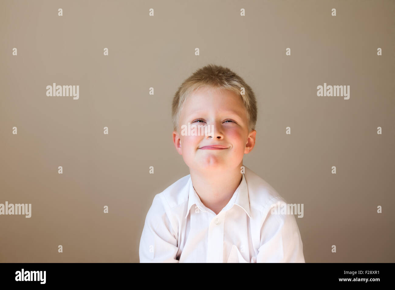 Funny tricky child (boy) thinking over grey background with copy space - Stock Image