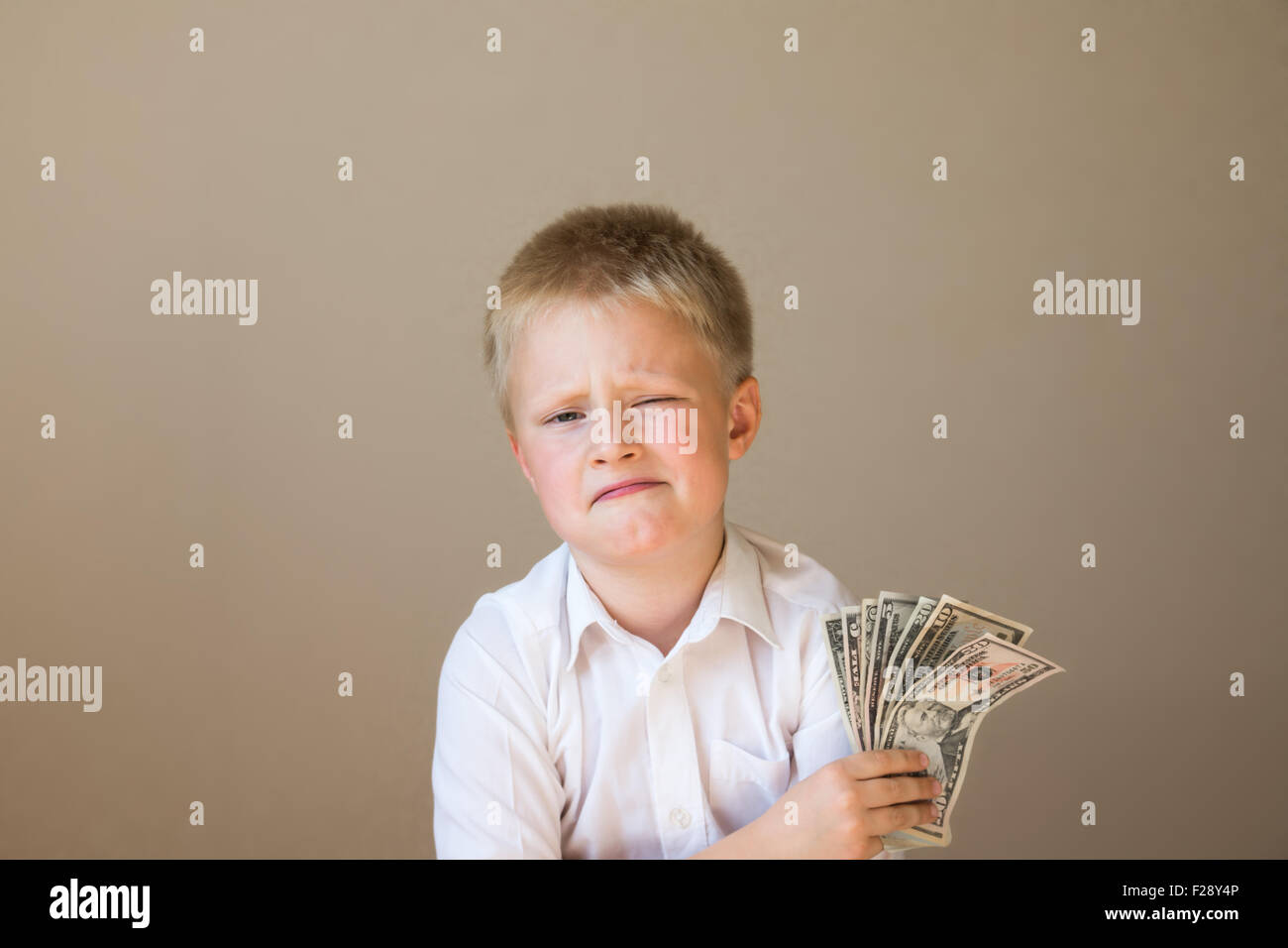 Happy smiling funny child with money (dollars) in hand on gray background - Stock Image
