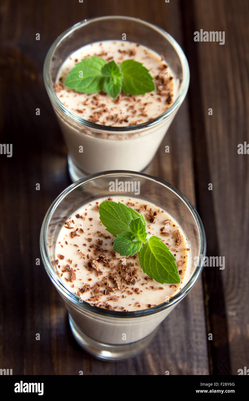 Chocolate Panna Cotta dessert with mint in portion glasses on dark wooden background - Stock Image