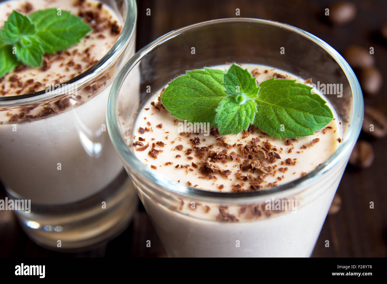 Chocolate Panna Cotta dessert with mint in portion glasses close up - Stock Image