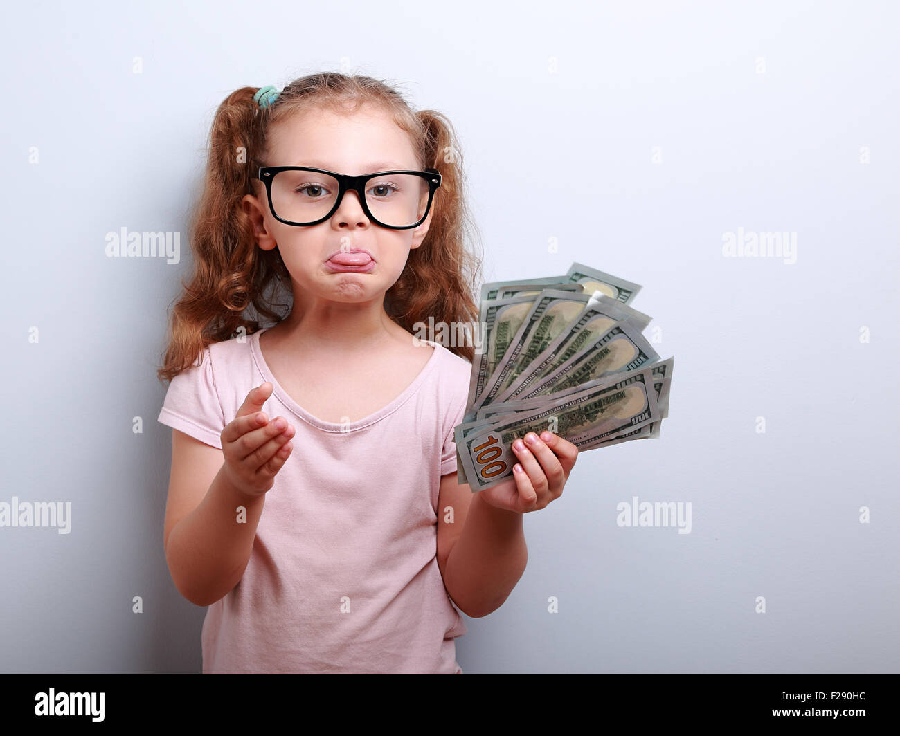 Fun grimacing kid girl explaining and showing tongue holding money in hand on blue background - Stock Image