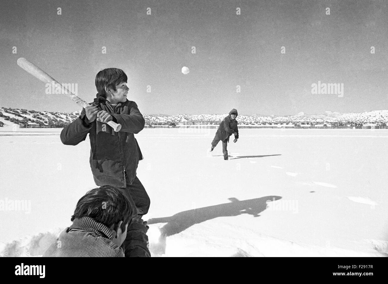 Cochiti Pueblo Indian boys playing baseball using a snowball on a winter day in 1970, Cochiti Pueblo, New Mexico - Stock Image