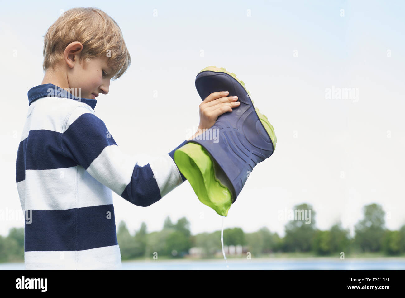 Boy pouring water out of a rubber boot, Bavaria, Germany - Stock Image