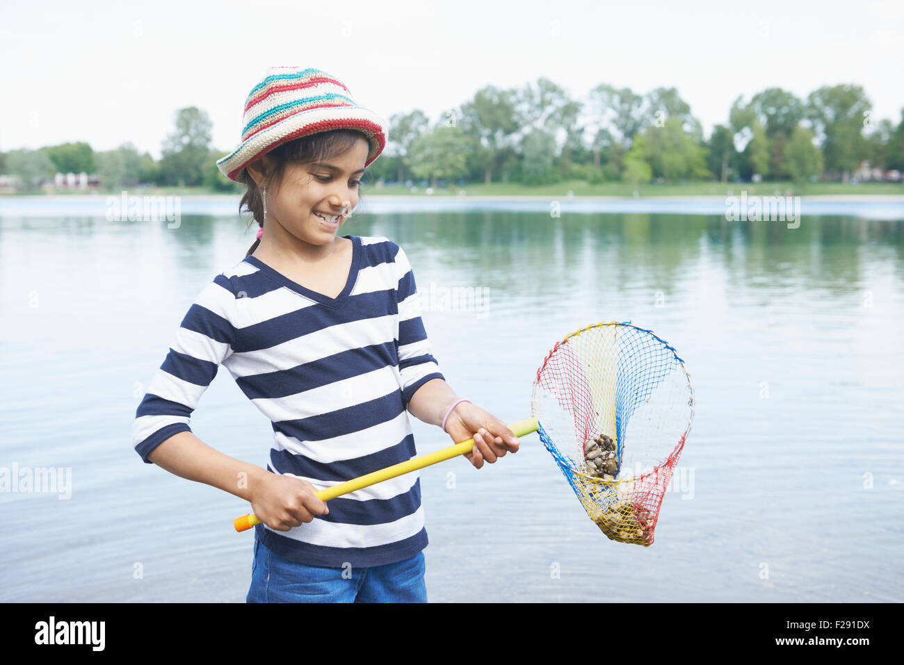 Girl holding stones in fishing net, Bavaria, Germany - Stock Image
