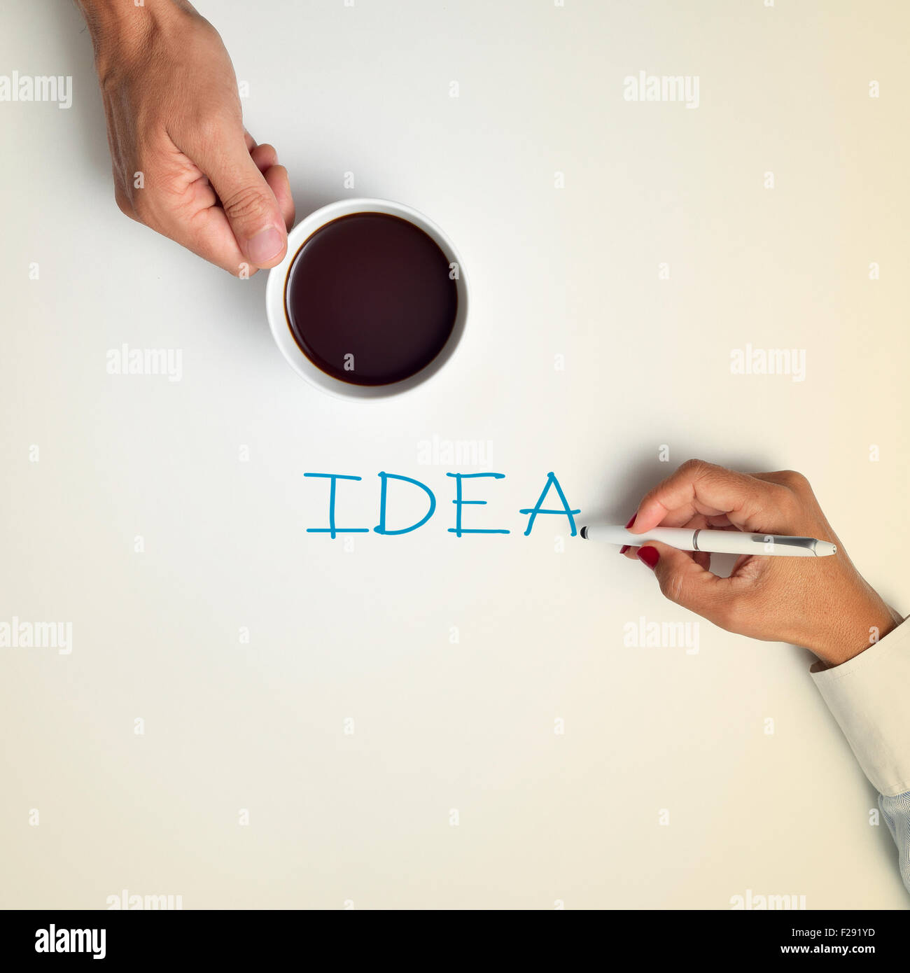 high-angle shot of a young man with a cup of coffee and a young woman writing the word idea with a pen - Stock Image
