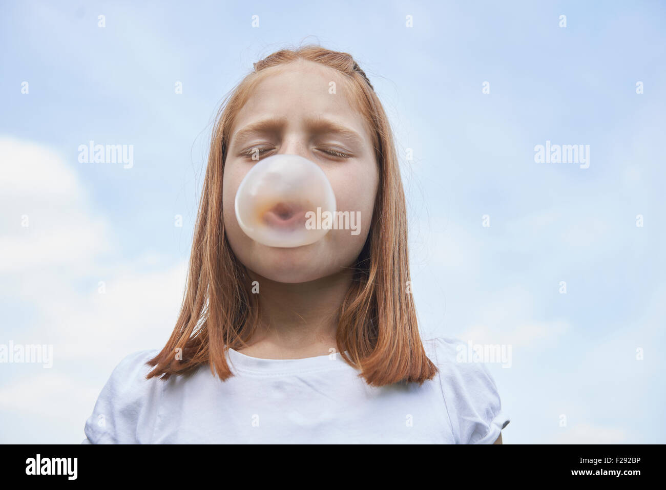 Girl blowing chewing gum bubble, Bavaria, Germany - Stock Image