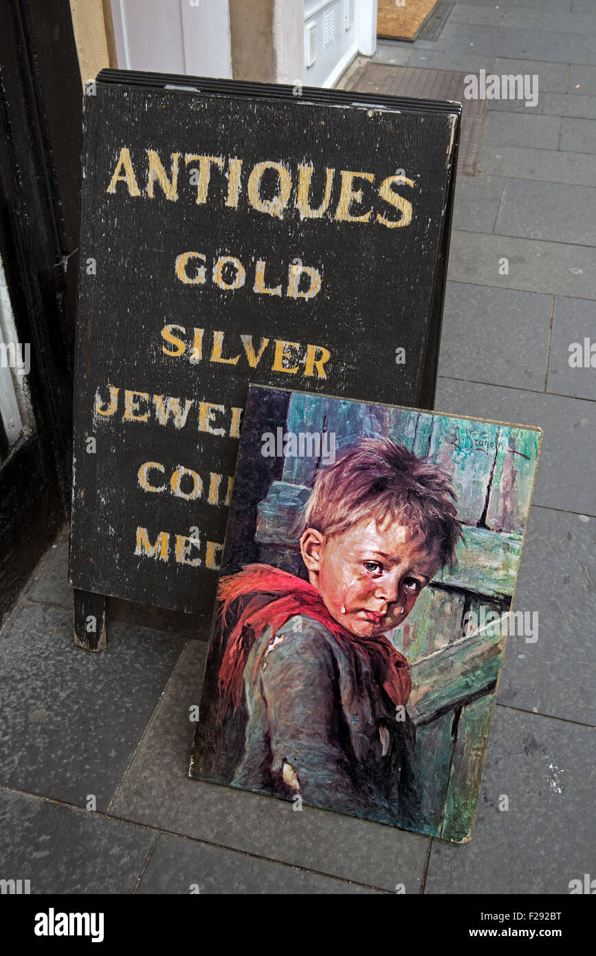Kitsch painting of a small boy crying next to an a-board sign outside an antique shop on Cockburn Street in Edinburgh's - Stock Image