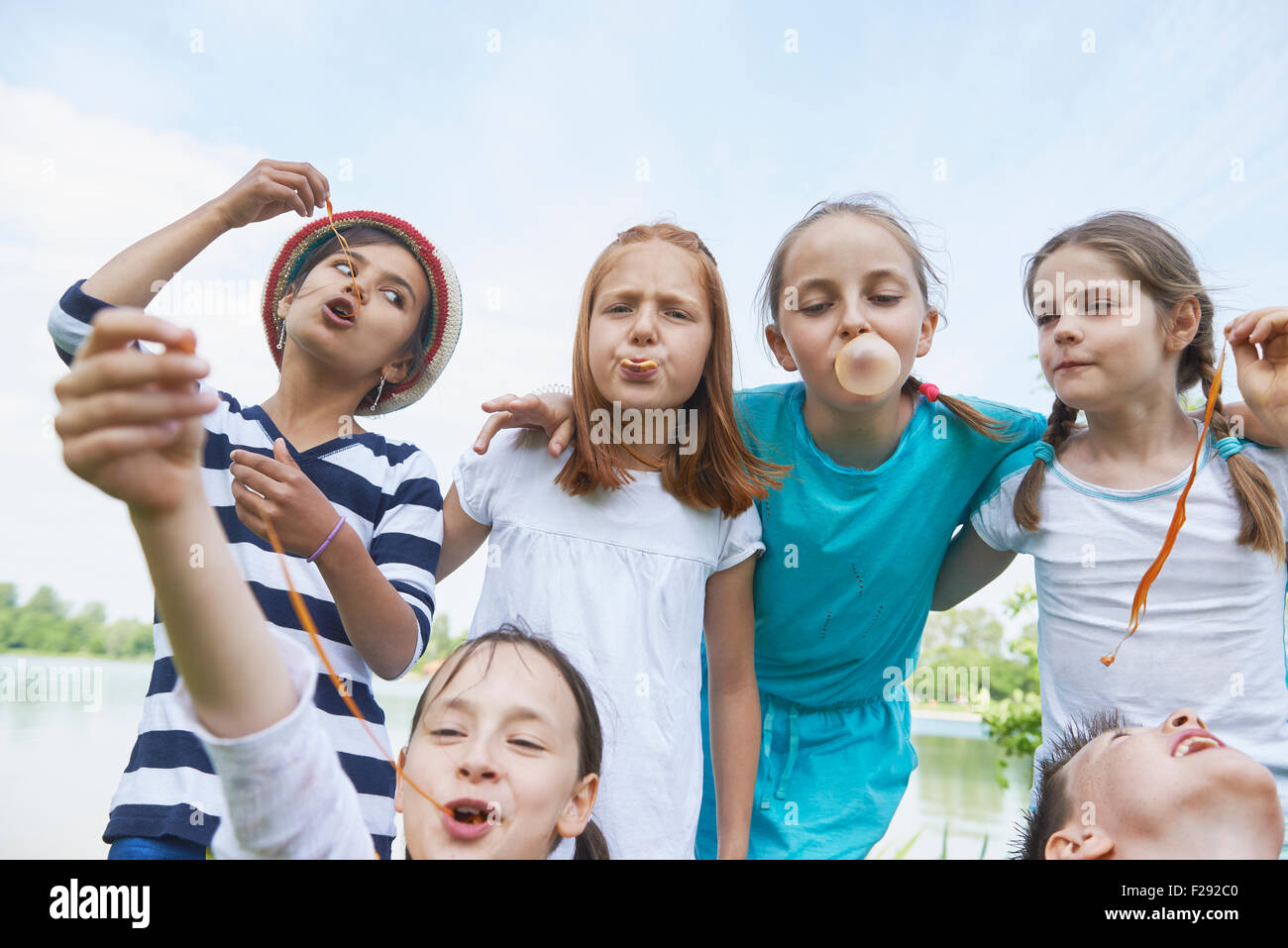 Group of friends playing with bubble gums, Bavaria, Germany - Stock Image